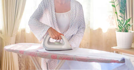 Closeup of woman ironing clothes ironing board Stockfoto - 128261202