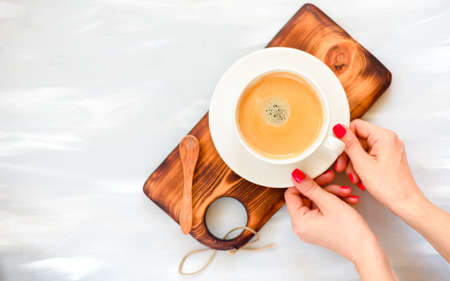 girls hands with red manicure holding coffee cup, flat lay, top view Stockfoto