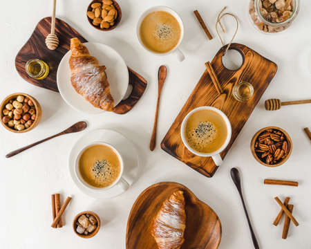 Continental breakfast captured from above (top view, flat lay). ?offee and croissants, nuts, cinnamon, pecan, hazelnut, honey, almonds, cutting board, wooden, spoon, lump sugar, free text (copy) space. Stockfoto - 128261254