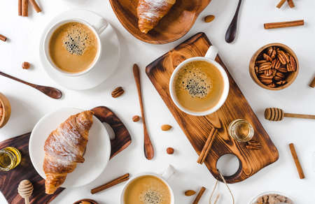 Continental breakfast captured from above (top view, flat lay). ?offee and croissants, nuts, cinnamon, pecan, hazelnut, honey, almonds, cutting board, wooden, spoon, lump sugar, free text (copy) space. Stockfoto - 128261253