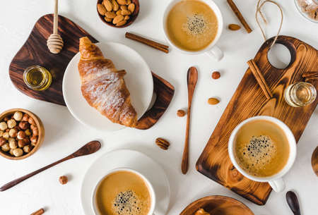 Continental breakfast captured from above (top view, flat lay). ?offee and croissants, nuts, cinnamon, pecan, hazelnut, honey, almonds, cutting board, wooden, spoon, lump sugar, free text (copy) space.