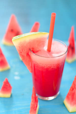 Watermelon smoothie in jars with fresh watermelon slices on blue background