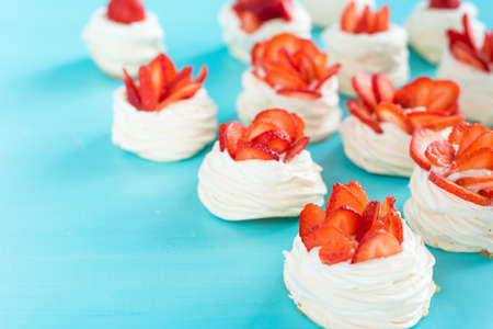 Beautiful pavlova cakes with strawberries on a blue  am. Stock Photo