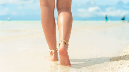 Beach travel concept. Sexy Legs on Tropical Sand Beach. Walking Female Feet. Closeup Archivio Fotografico - 129843574