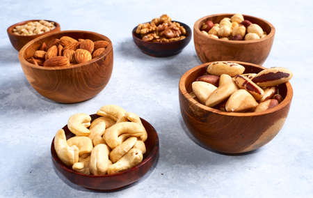 Almonds, walnuts and hazelnuts in wooden bowls on wooden Stock Photo