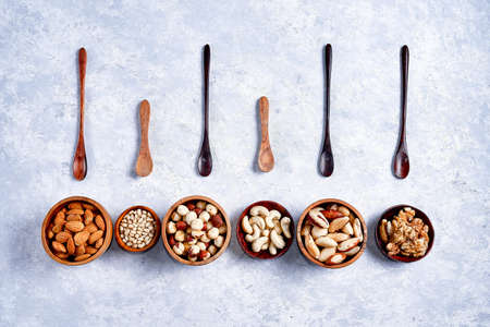 Nuts in wooden bowls on blue Banco de Imagens