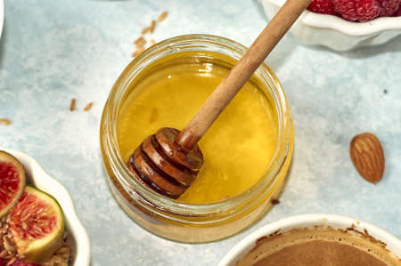 Honey and honey spoon in a jar on table