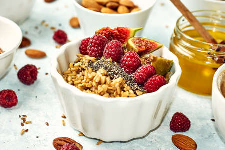 Oatmeal porridge with raspberry and figs in bowl