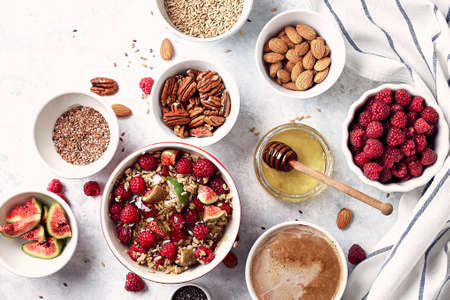 Ingredients for a healthy breakfast, oatmeal with raspberries, figs, pecans, almonds, flax seeds, chia seeds with honey and coffee. Good morning, health concept.