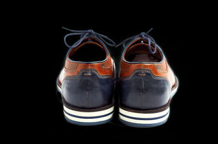 luxurious male brown and blue leather shoes isolated on a black , top view