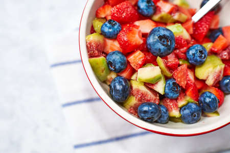 bowl of fruit salad fig strawberry blueberry, concept diet and healthy eating
