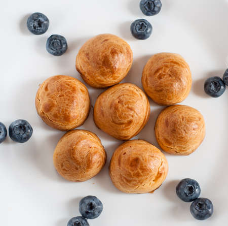 dessert profiteroles with Blueberries on a white plate