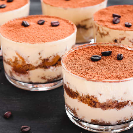 gourmet tiramisu dessert in a glass sprinkled with cocoa and decorated with coffee beans on a dark background Stok Fotoğraf