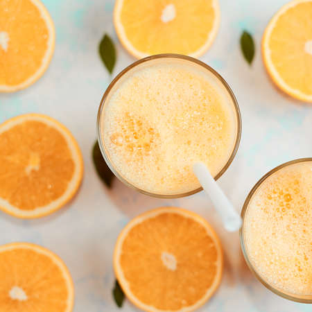 Orange smoothie in glass, top view. Flat lay
