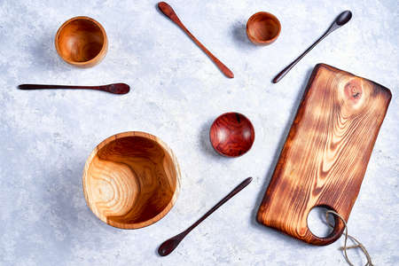 Eco-friendly wooden bowls, spoons on blue background, flat lay, top view.