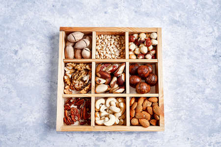 pecans, hazelnuts, almonds, pine nuts, brazil nut, cashews in a wooden box on blue background, top view, 写真素材