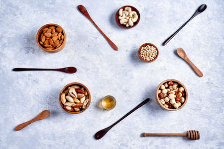 hazelnuts, almonds, pine nuts, Brazil nut, cashews in wooden bowls on blue background, top view, flat lay 写真素材 - 130627193