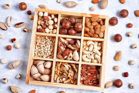 pecans, hazelnuts, almonds, pine nuts, brazil nut, cashews in a wooden box on blue background, top view, 写真素材 - 130627283