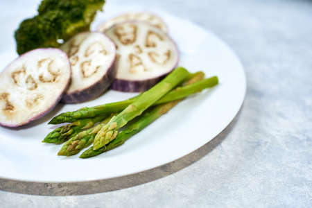 Steamed vegetables in a white plate on a blue table. Eggplant, broccoli, asparagus.