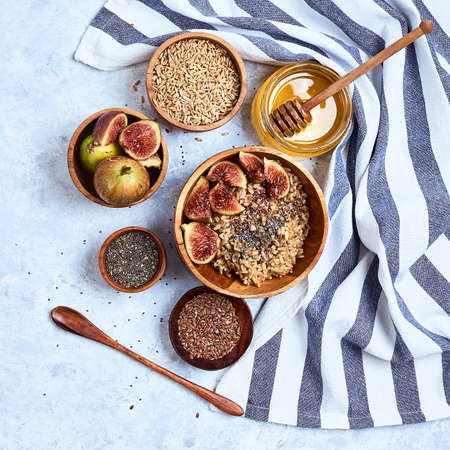 Healthy breakfast and breakfast ingredients, oatmeal with figs, flax and chia seeds, honey. Top view
