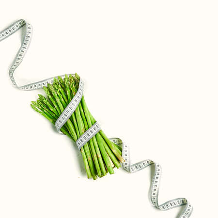 creative layout asparagus with measuring tape concept diet, healthy lifestyle, diet, vegetarian, top view.
