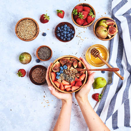 Top view showing hands eating porridge with honey nuts, blueberries on white wooden table selective focus, blurred background Good morning - healthy breakfast background Archivio Fotografico - 131415732