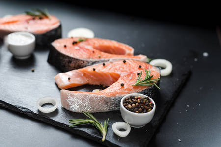 raw salmon steak on a dark stone background with onions, rosemary, spices, concept diet, unsaturated fats.