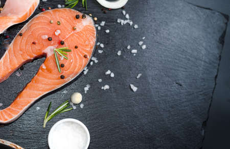 Two salmon steak, butter, pepper and salt, lemon, herbs border ,place for text on wooden rustic background top view Stok Fotoğraf