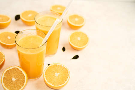 freshly squeezed orange juice in glasses on the kitchen table with slices of oranges, concept of healthy lifestyle