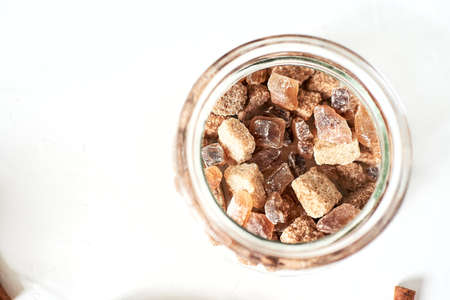 brown cane sugar lump in a sugar bowl, top view. Concept diet, junk food, health, lifestyle.
