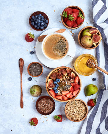 Healthy breakfast and breakfast ingredients, oatmeal with fruits and berries, figs, blueberries, strawberries, flax and chia seeds, honey.