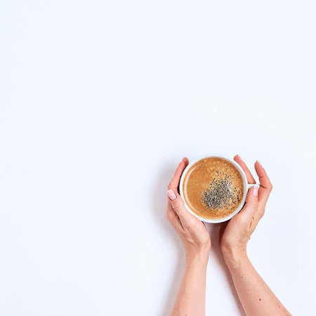 Coffee cup in female hands on a white background. Top view