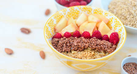 healthy breakfast oatmeal with fruits, raspberries, peach, flax seeds, nuts, good morning concept, healthy food
