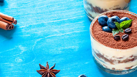 dessert tiramisu in glasses, decorated with blueberries and mint with coffee beans
