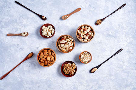 pecans, hazelnuts, almonds, pine nuts, cashews in wooden bowls on blue background, top view