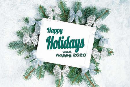 Composizione piatta con la scritta buone feste e buon 2020 . Cornice con rami di albero di natale, decorazioni natalizie Archivio Fotografico