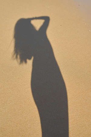 shadow from the photographer girl in the sand, silhouette in the sand, wave Stock Photo