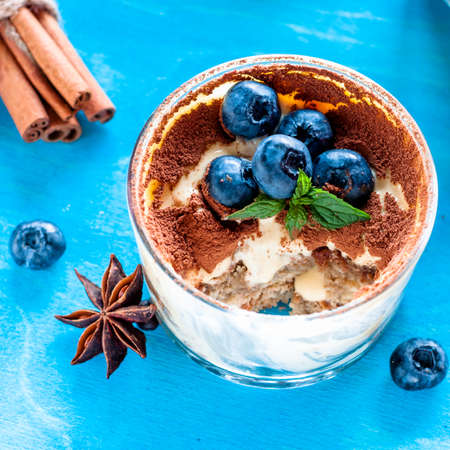 Dessert tiramisu in glasses, decorated with blueberries and mint with coffee beans Stock Photo