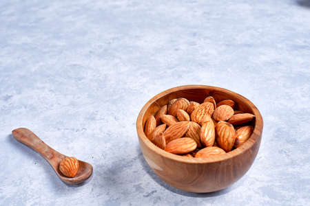 Almonds in brown bowl on a wooden
