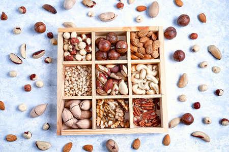 Pecans, hazelnuts, almonds, pine nuts, brazil nut, cashews in a wooden box on blue