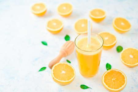 Glass of freshly squeezed orange juice and slices of orange fruit isolated on white background