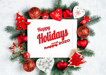 happy holidays lettering in frame with christmas decorations in red Standard-Bild - 134827373