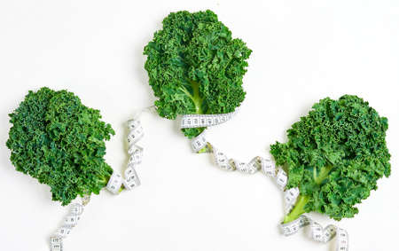 creative layout kale with measuring tape, concept diet, healthy lifestyle, diet, vegetarian, top view