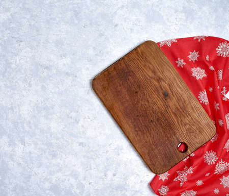 Empty kitchen cutting board with red christmas tablecloth.