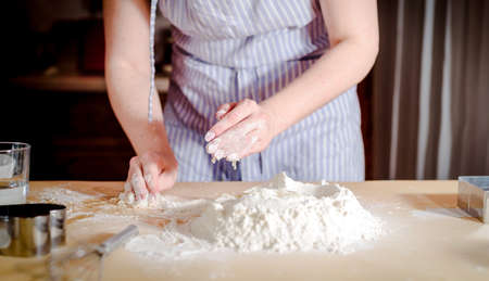 Chef kneads  dough on wooden table Stock fotó