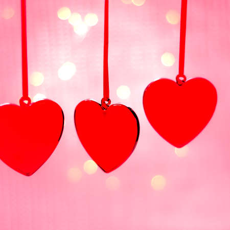 Hanging crimson Christmas Heart toy on  glowing colorful