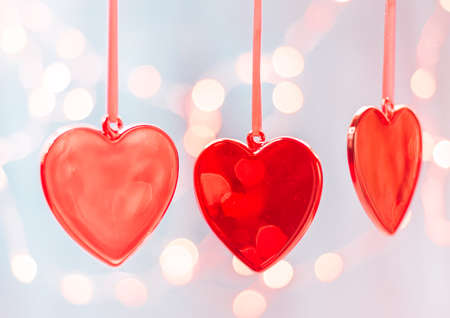 Hanging crimson Christmas Heart toy on on a glowing colorful