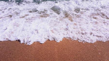 Sea waves on golden sand, white sea foam.