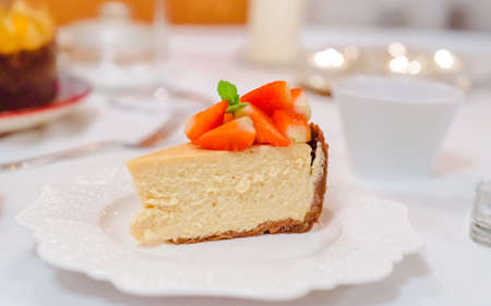 Fresh strawberry cheesecake on a ceramic plate on a white table