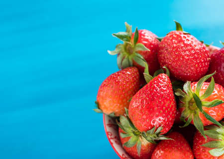 strawberries in a colorful bowl on colorful background
